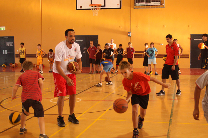 Kyle Jeffers teaching a kid how to dribble